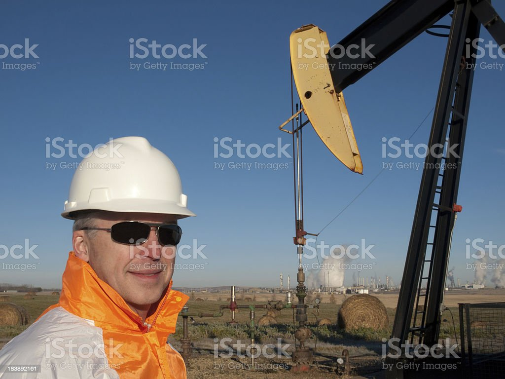Oil Worker in Safety Gear at Well Pumpjack royalty-free stock photo