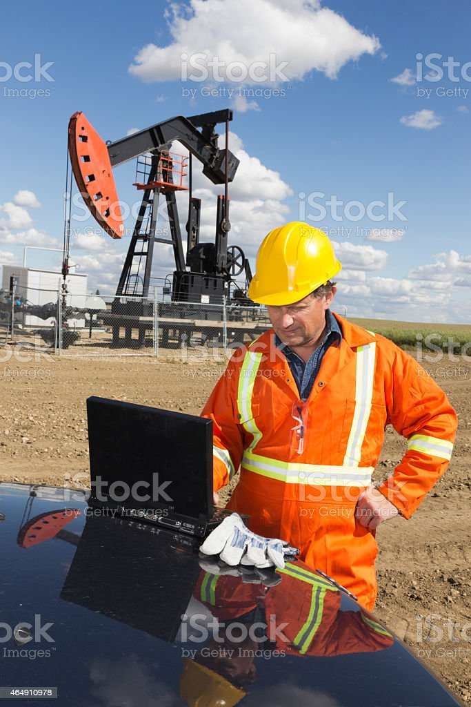 Oil Worker Surfing the Web using  Computer at a Pumpjack stock photo