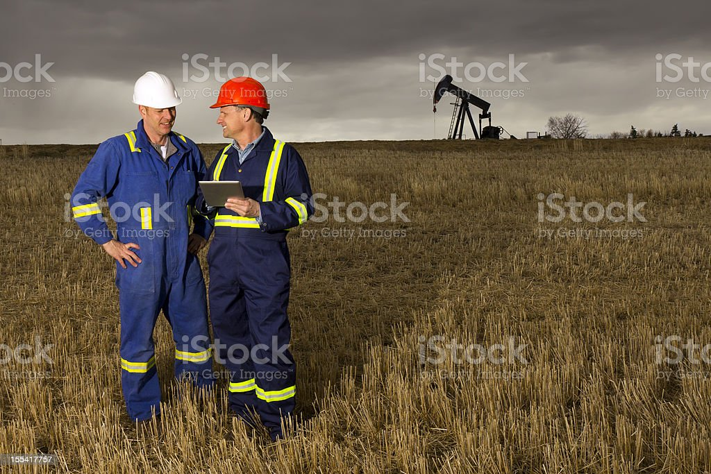 Oil Workers and Digital PC royalty-free stock photo
