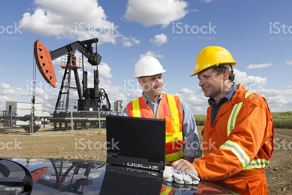 Oil Workers and Laptop stock photo