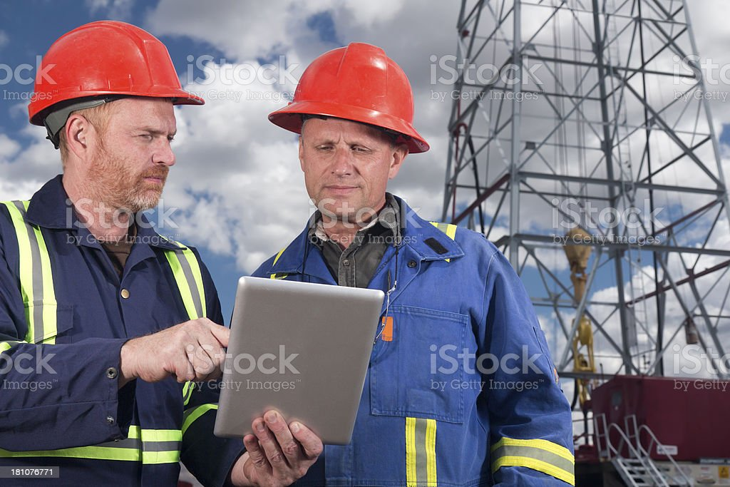 Oil Workers and Technology stock photo