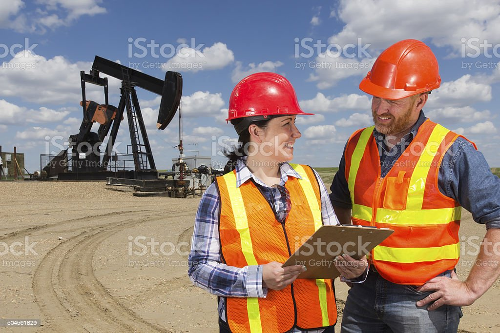 Oil Workers at a Pumpjack stock photo