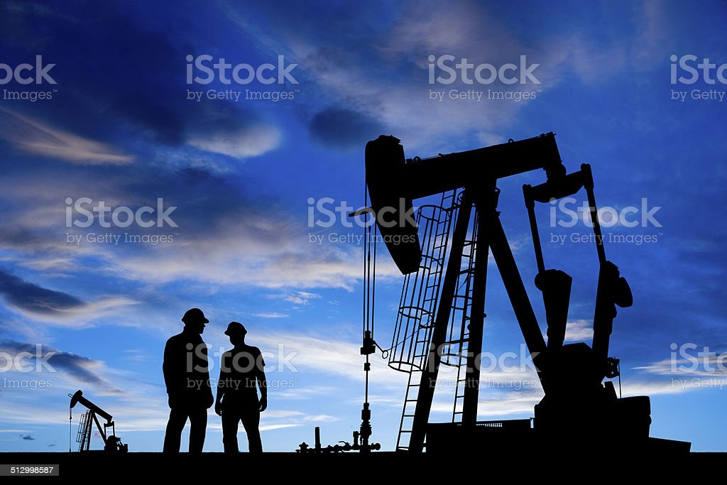 Oil Workers at Dusk stock photo