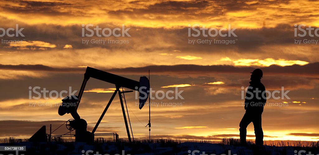 Oilfield Worker at Sunrise by Pumpjack stock photo