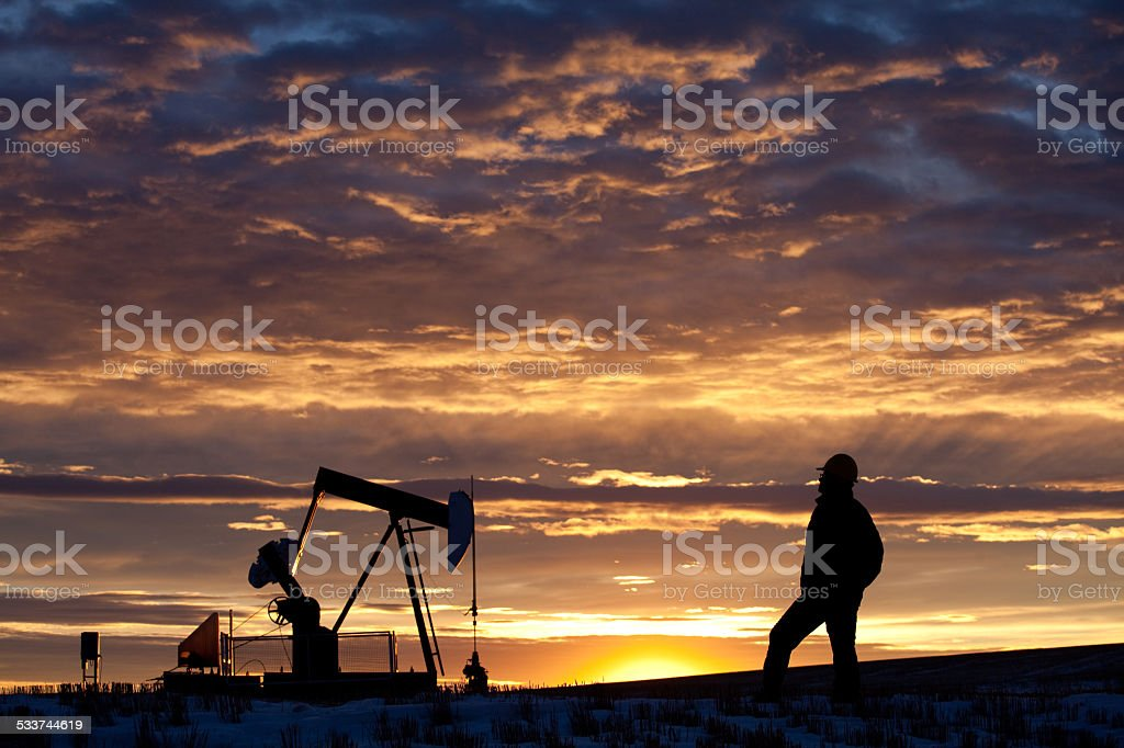 Oilfield Worker or Geologist at Sunrise by Pumpjack stock photo