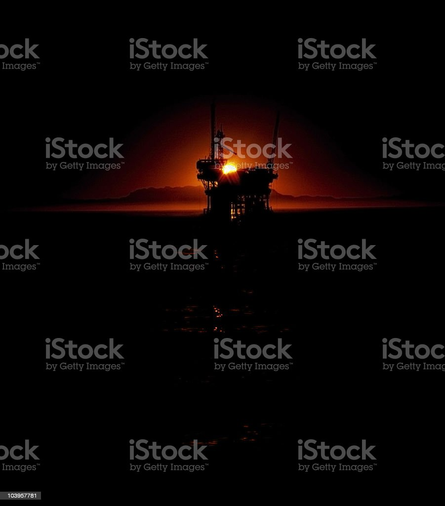 oil-well at sunset stock photo