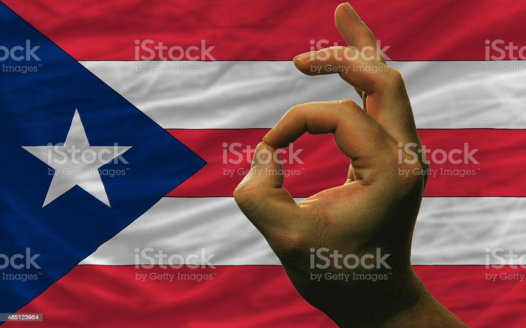 ok gesture in front of puerto rico national flag stock photo