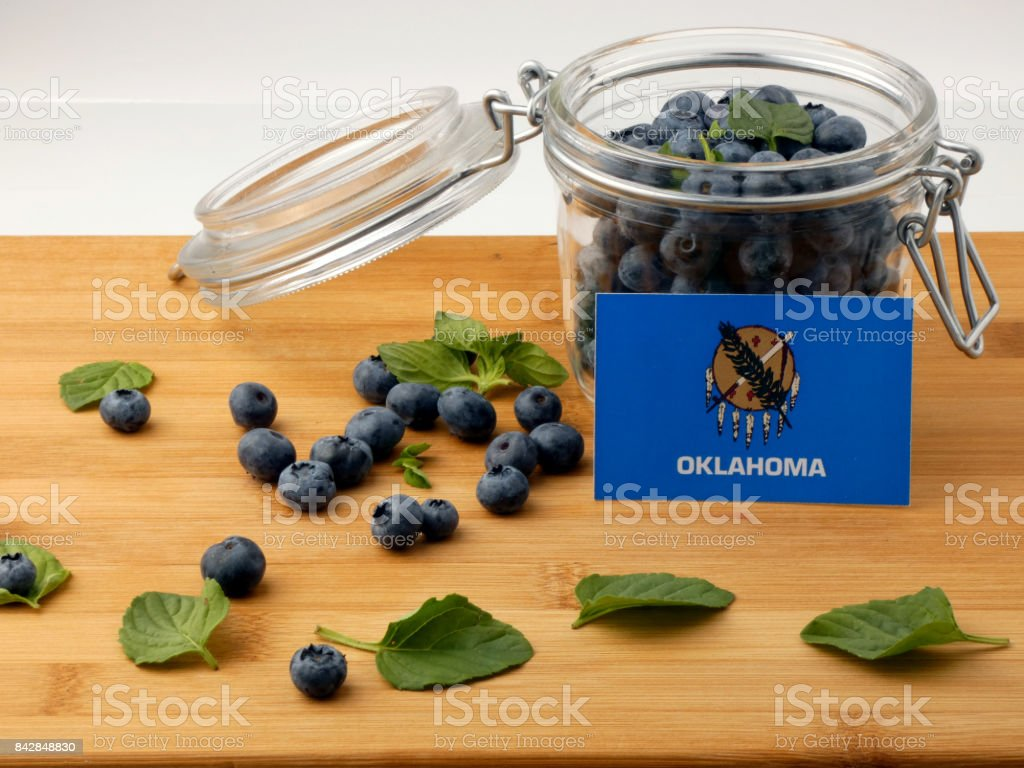 Oklahoma flag on a wooden plank with blueberries isolated on white stock photo