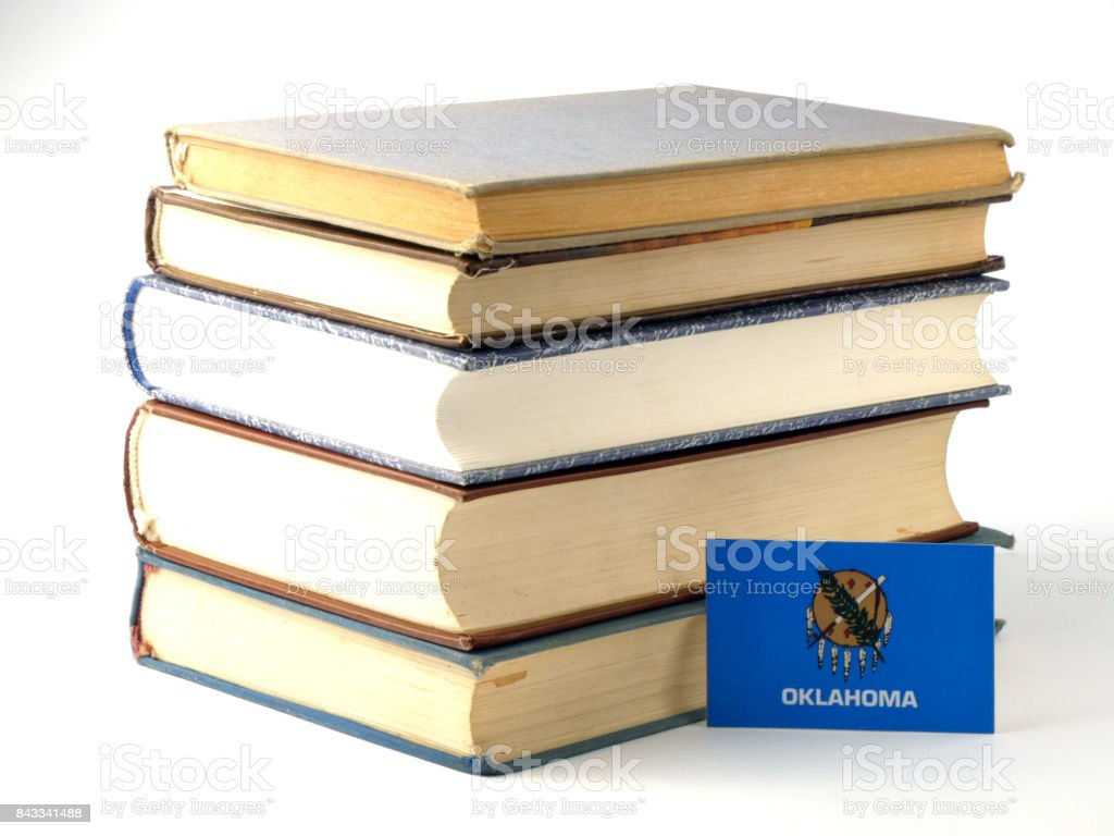 Oklahoma flag with pile of books isolated on white background stock photo