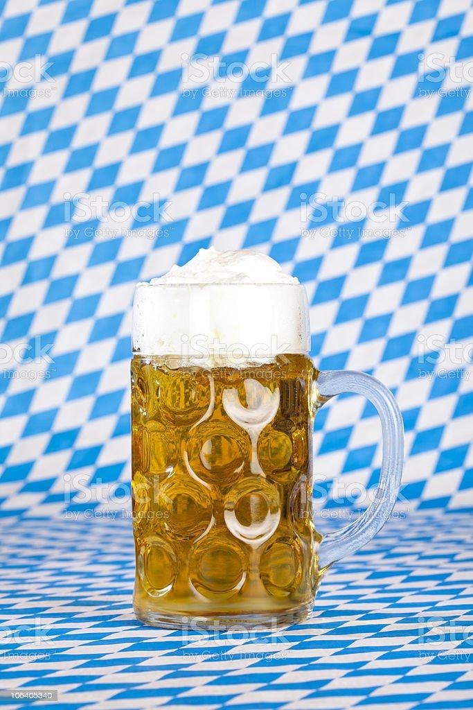 Oktoberfest Maßkrug mit Schaumkrone und bayerischer Flagge royalty-free stock photo