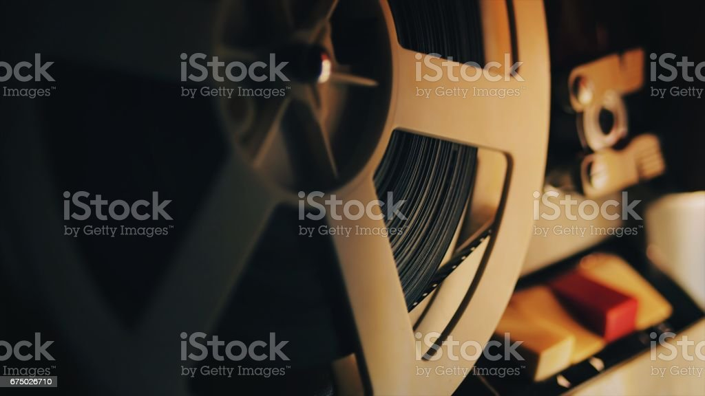 Old 8mm film projector playing in the night. Close-up of a reel with a film stock photo