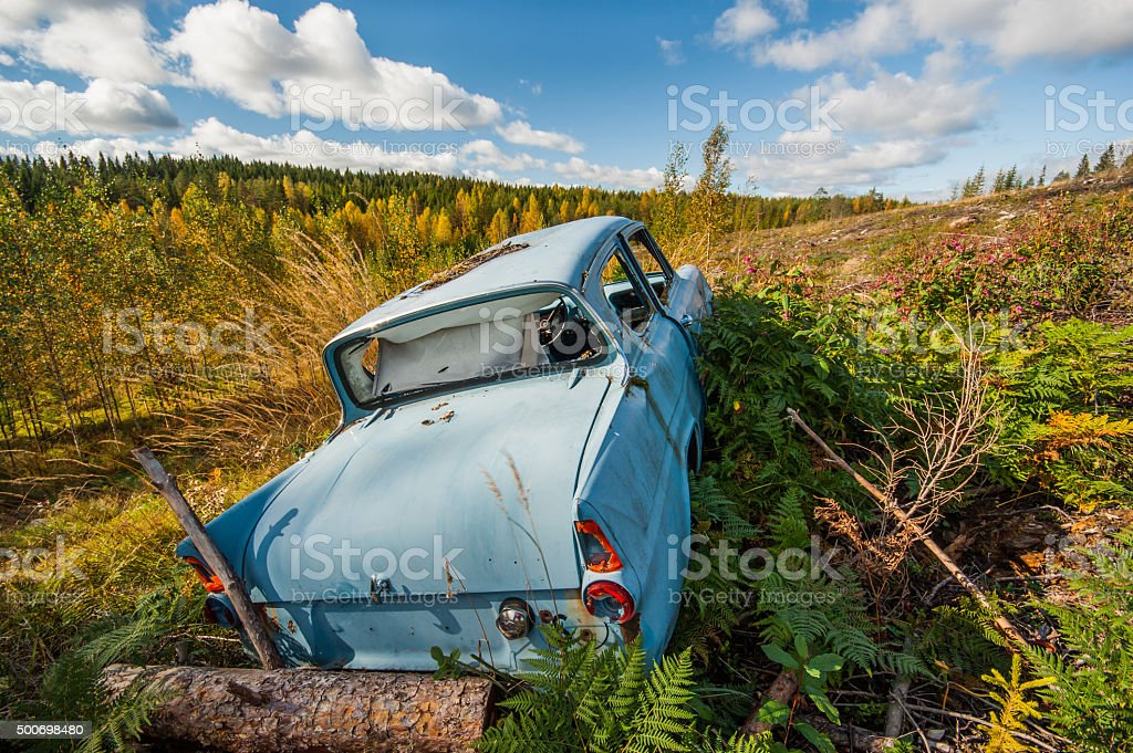 Old abandoned car on a field stock photo
