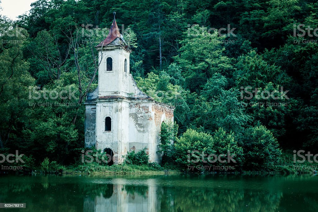 Old abandoned church and lake in Transylvania, Romania stock photo