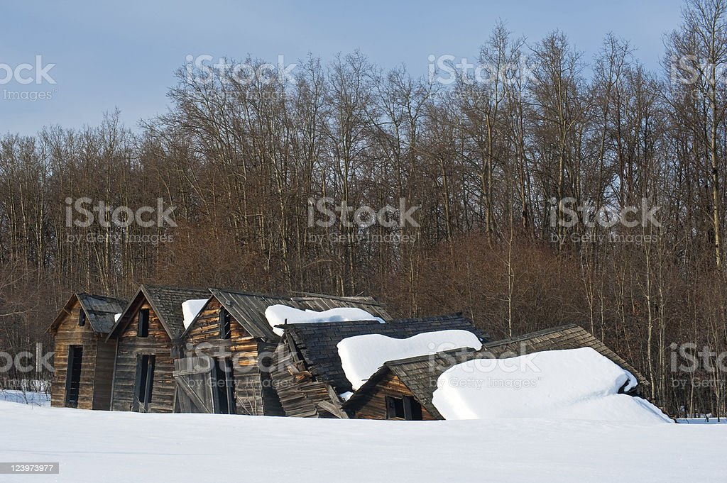 Old abandoned farm building: collapsing snowy granaries royalty-free stock photo
