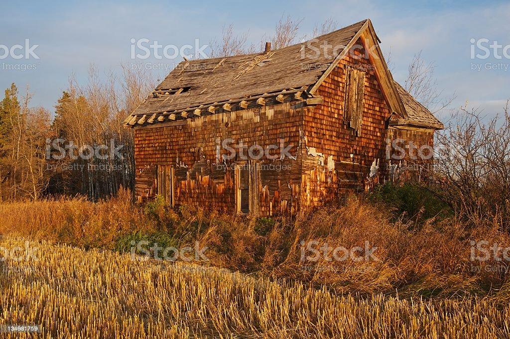 old abandoned farm house: farmhouse lit by the rising sun stock photo