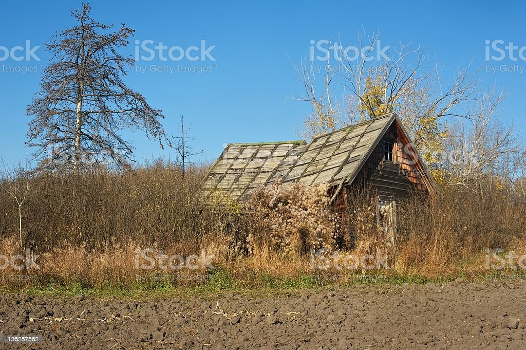 old abandoned farmhouse:  collapsing house behind a cultivated field stock photo