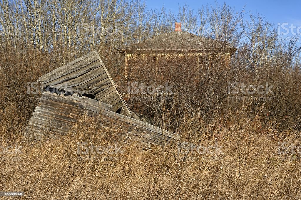old abandoned farmhouse: derelict house and collapsed shed stock photo
