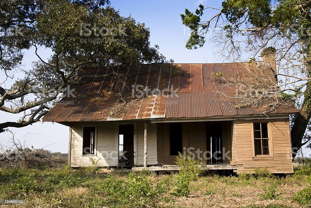 Old, abandoned home. House is wooden with rusty tin roof. royalty-free stock photo