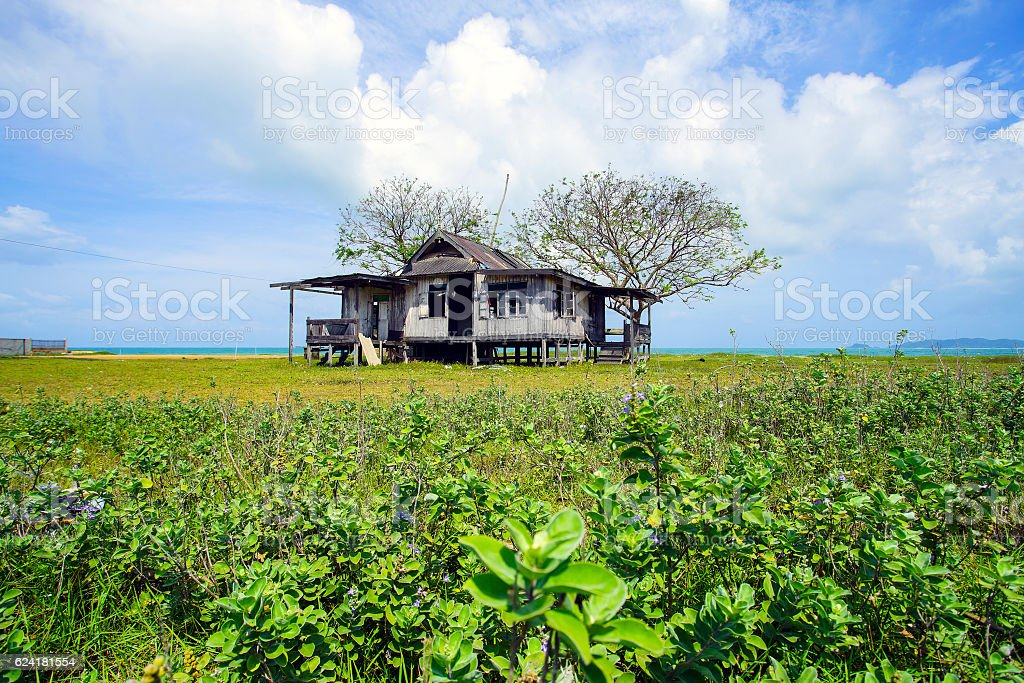Old abandoned house under blue sky near the beach. stock photo