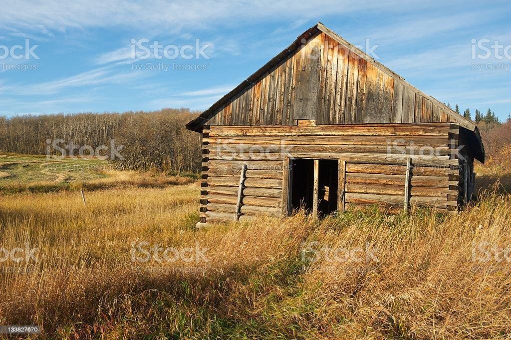 old abandoned log cabin on grassy hillside royalty-free stock photo