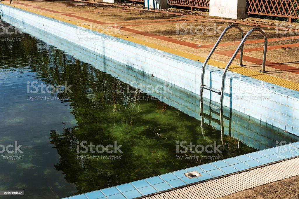 Old abandoned swimming pool with dirty water stock photo