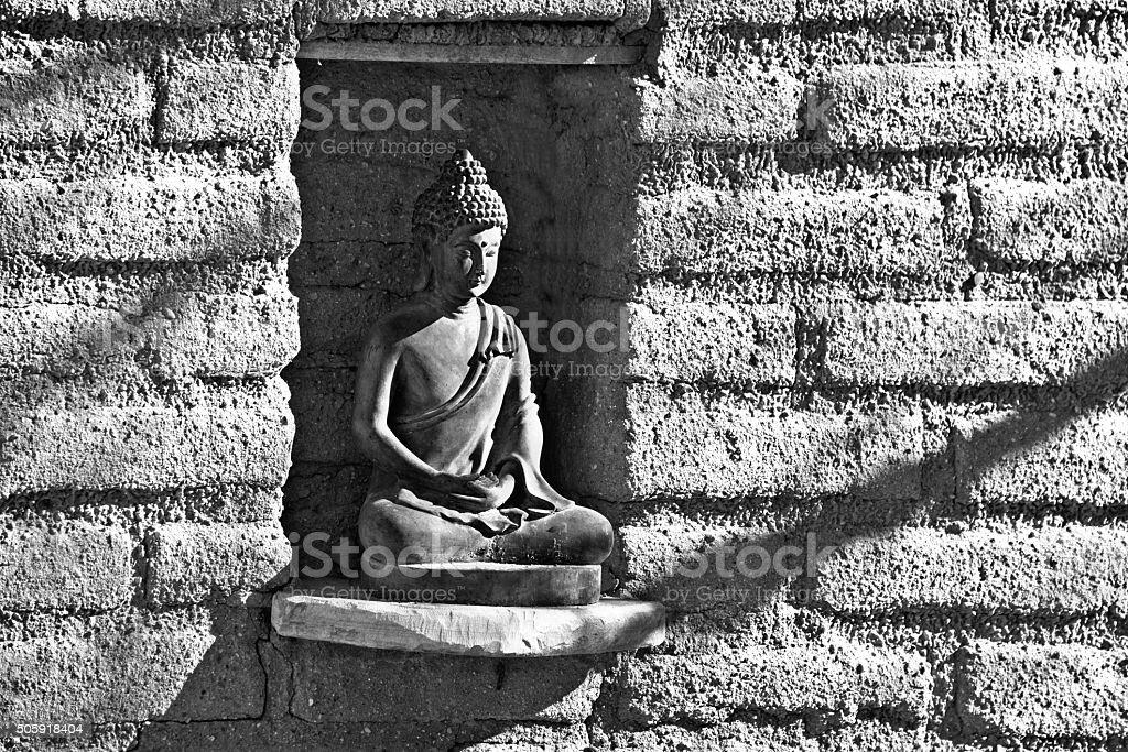 Old Adobe Wall Niche, Buddha Statuette, Sunlight, Full Frame Image stock photo