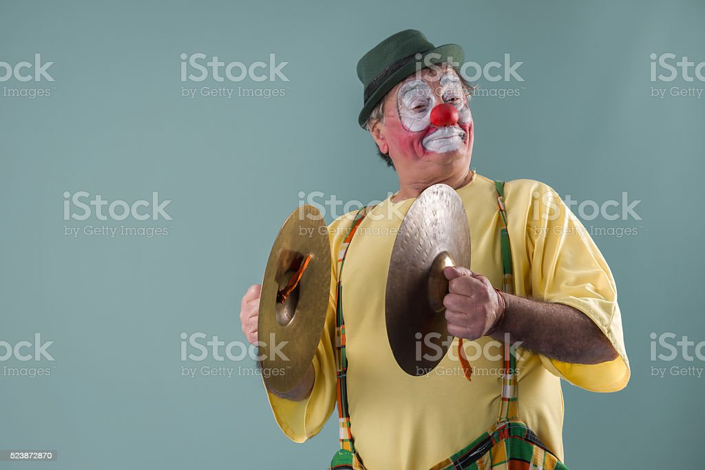 Old -aged clown with  clash cymbals stock photo