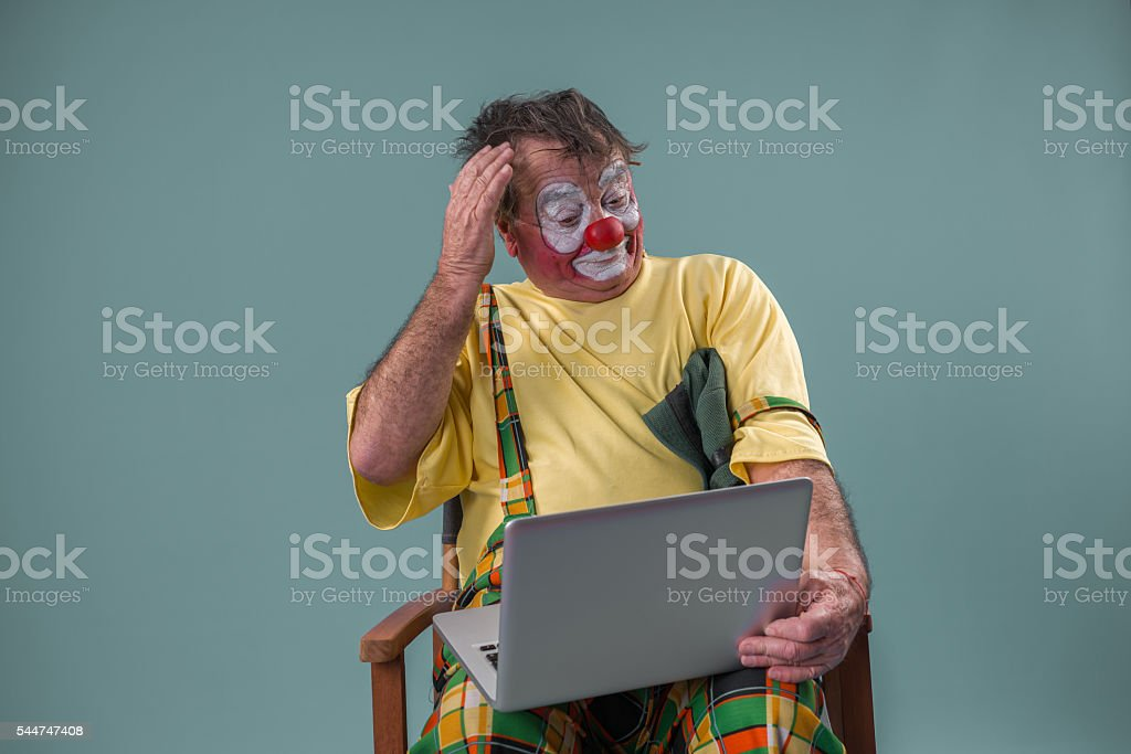 Old -aged clown with laptop stock photo