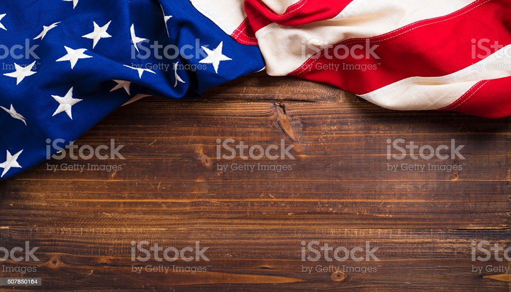 Old American Flag on wooden plank background stock photo