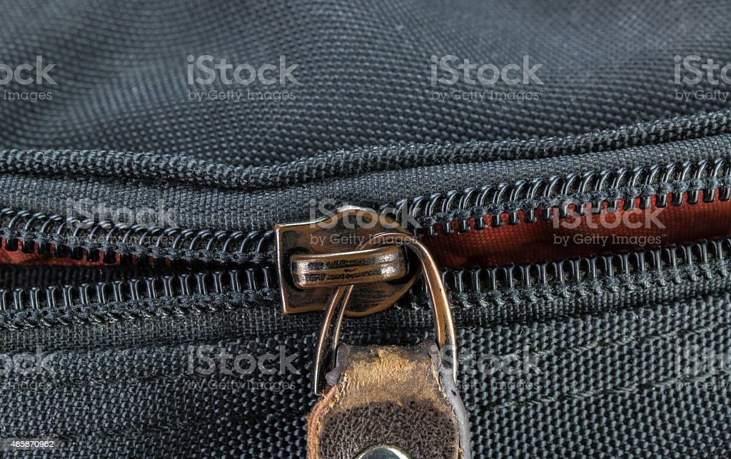 Old and damaged zipper on black cloth stock photo