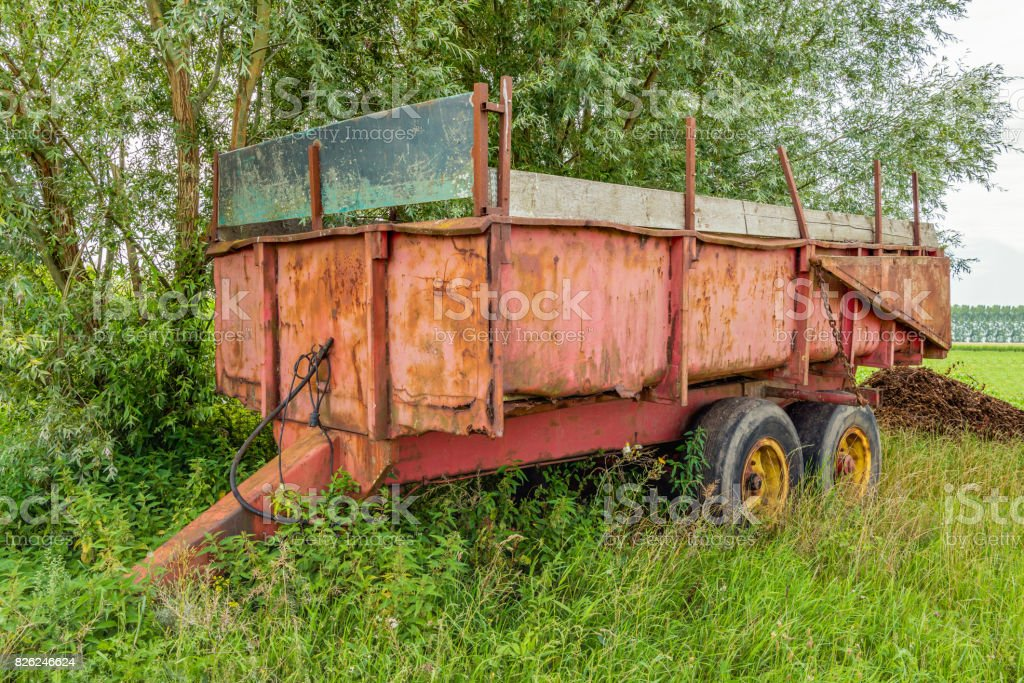 Old and rusty farm trailer stock photo