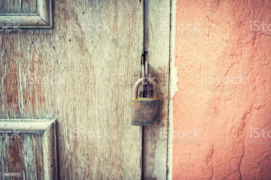 Old and rusty padlock on a wooden door stock photo