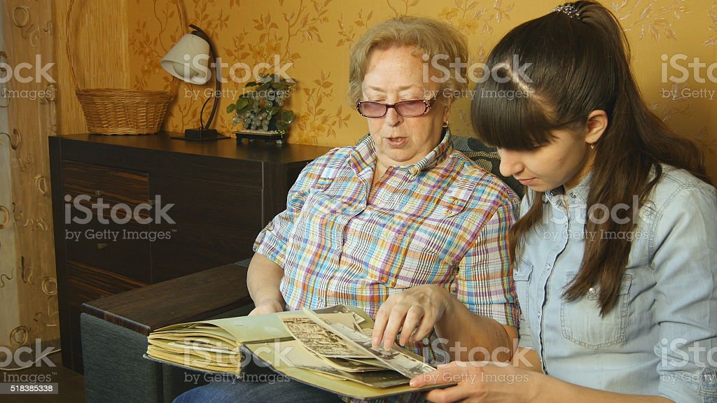 Antigua y mujer joven observando a familia álbum de fotos foto de stock libre de derechos