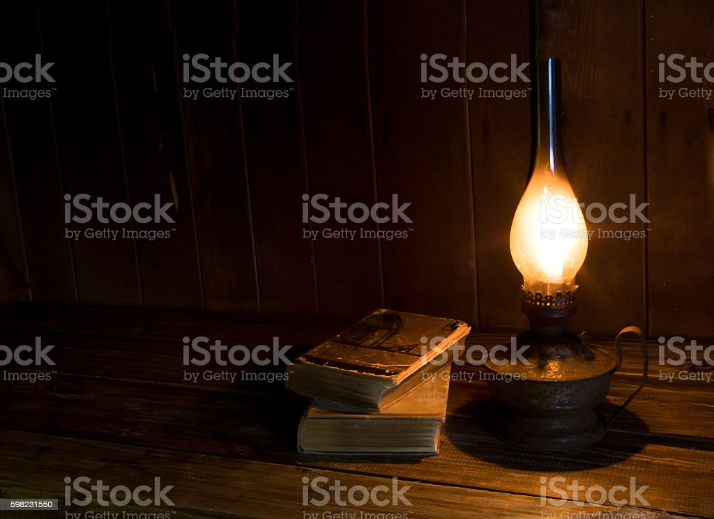 Old antique books with burning paraffin lamp. stock photo