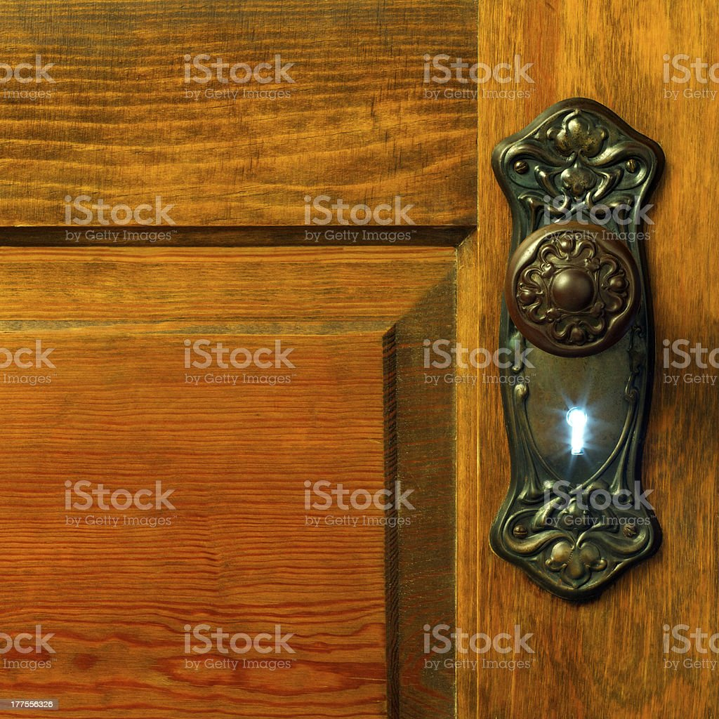 Old antique door and handles with an illuminated key hole stock photo