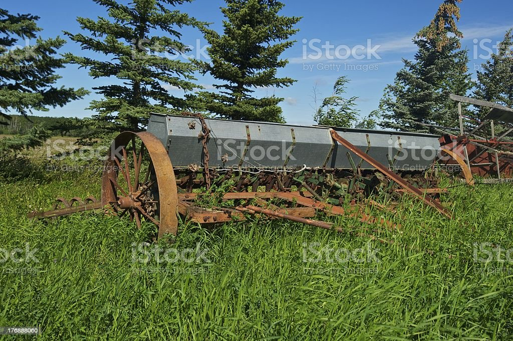 old antique farm machinery: abandoned seeder stock photo