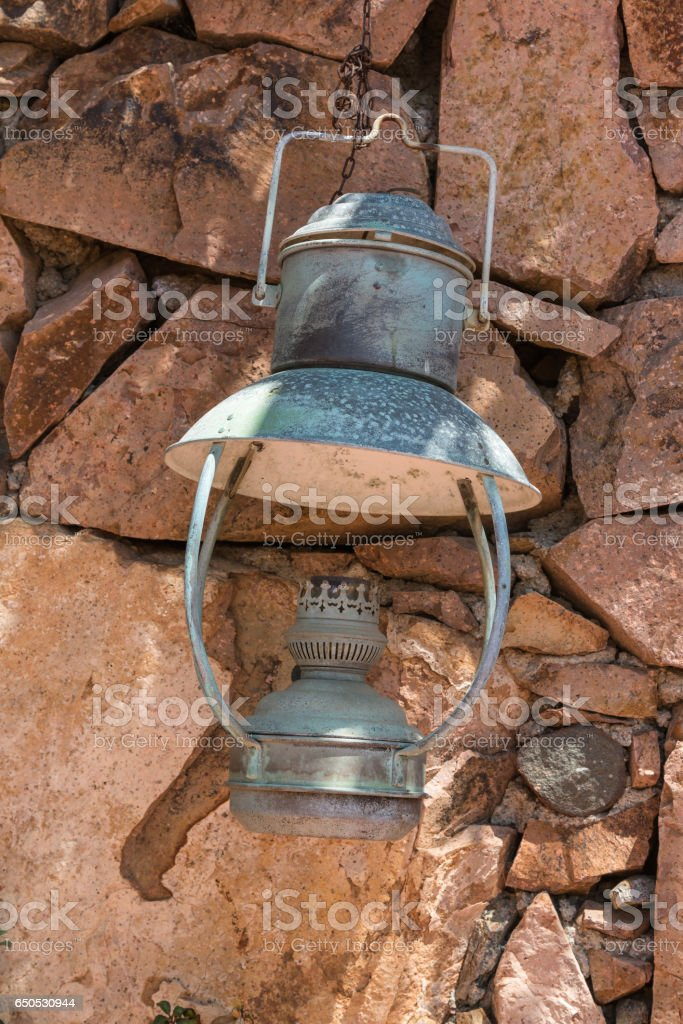 Old Antique Oil Lantern Hanging on a Stone Wall stock photo