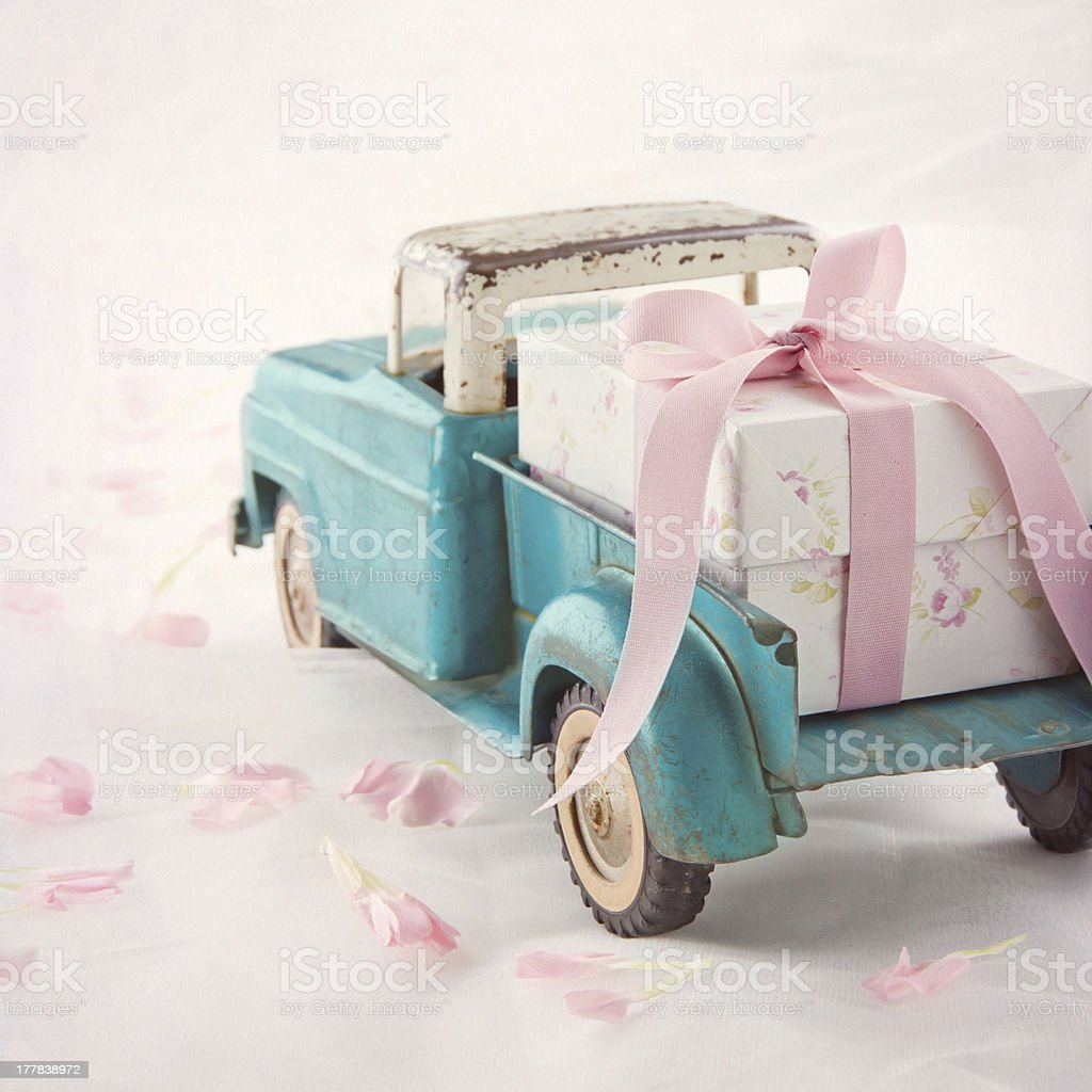 Old antique toy truck carrying a gift box stock photo
