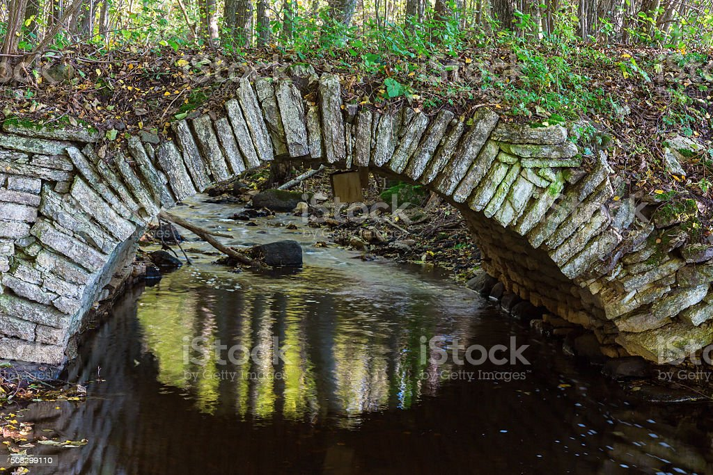 Old arch bridge over creek in the woods stock photo