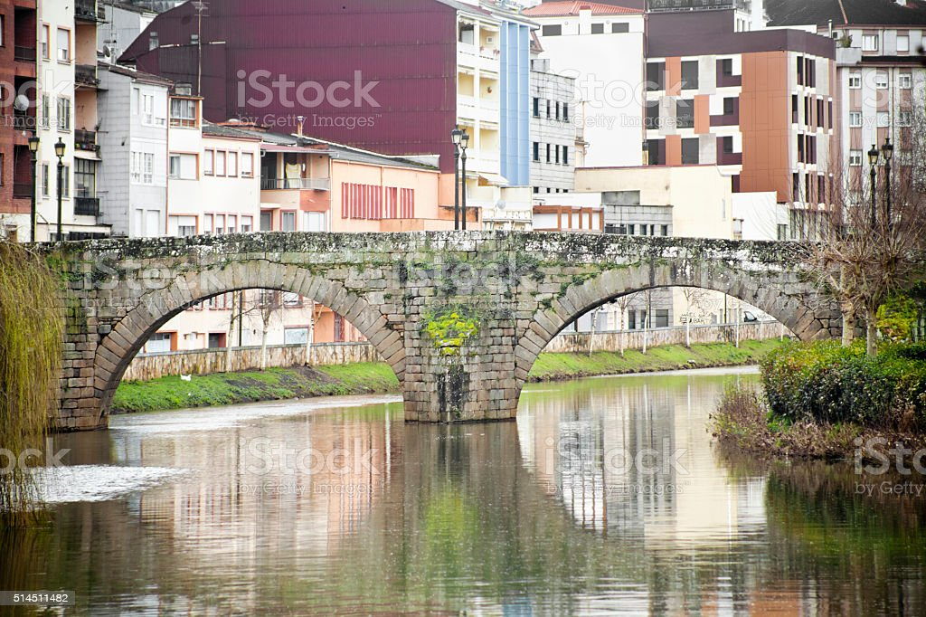 Old arched stone bridge, apartment buildings, Monforte, Galicia, Spain. stock photo