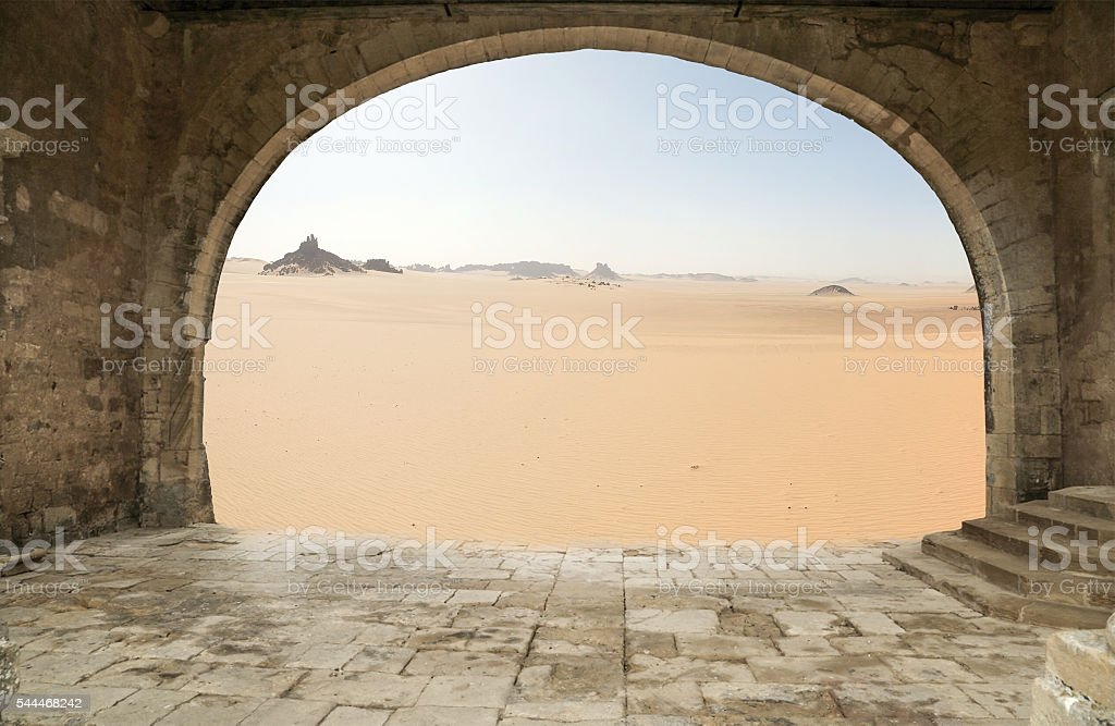 Old architectural arch in the background of the desert. stock photo