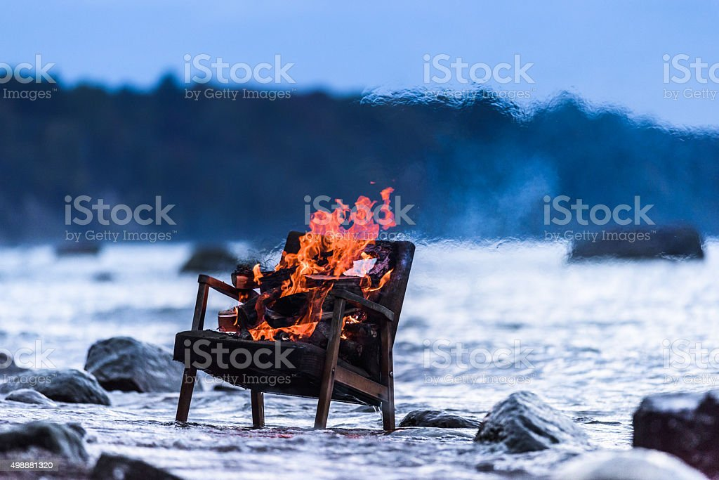 Old armchair in fire stock photo