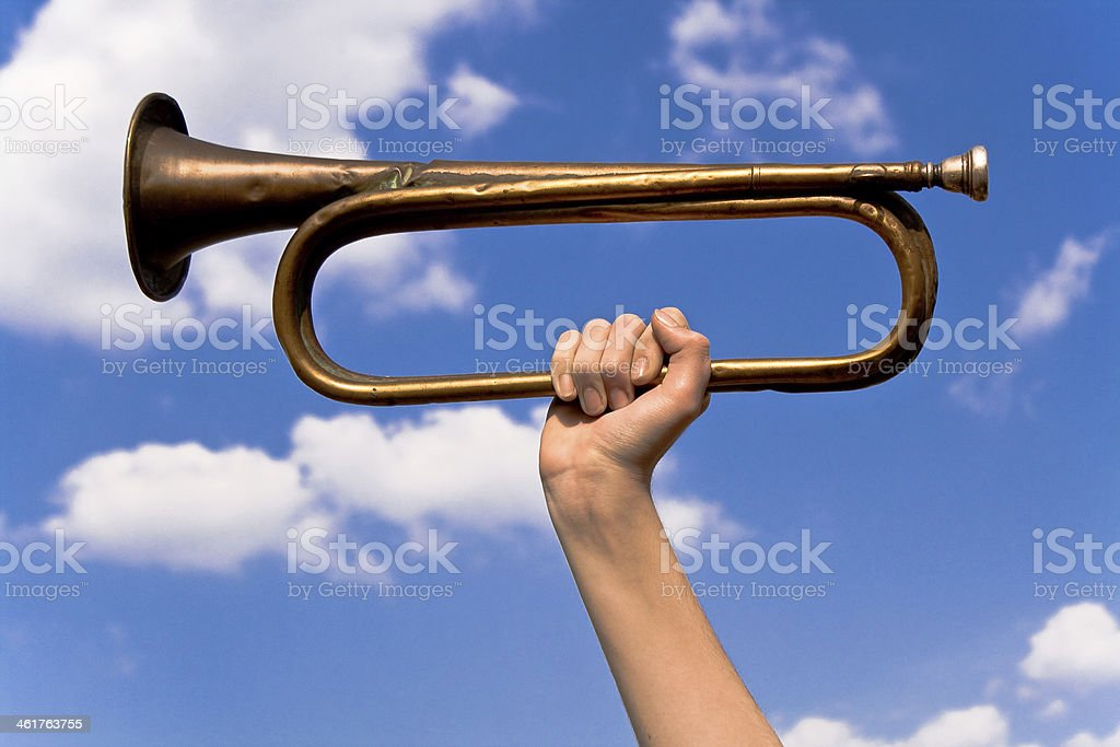 Old army trumpet in hand over blue sky stock photo