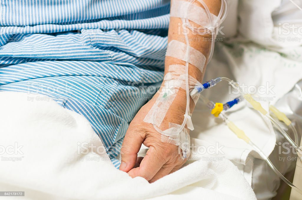 Old Asian man patient is on drip receiving saline solution stock photo