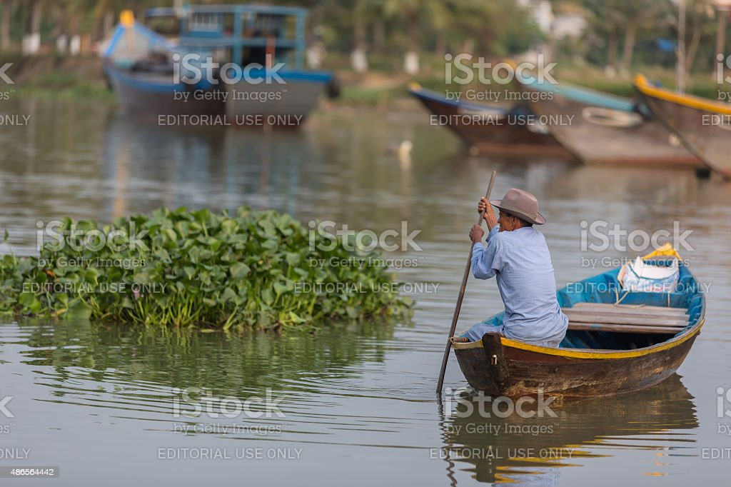 Old Asian man sitting on a boat stock photo