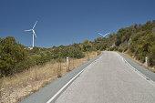 Old asphalt road climbs hill towards wind turbines