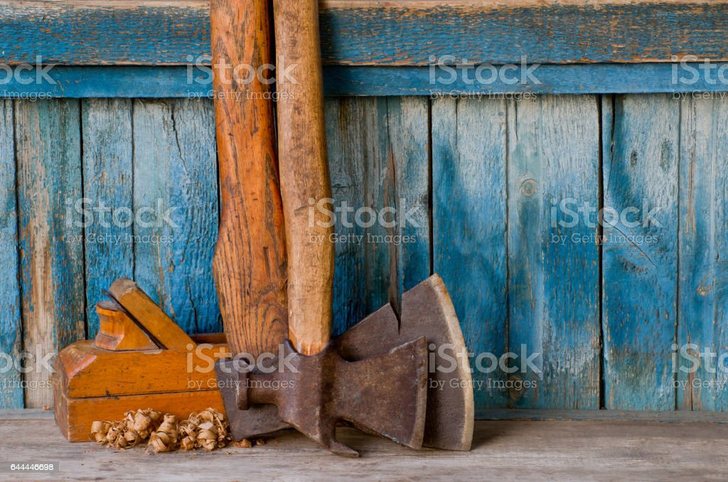 Old ax, pickaxe, wooden plane and chips on a background of the old wall stock photo