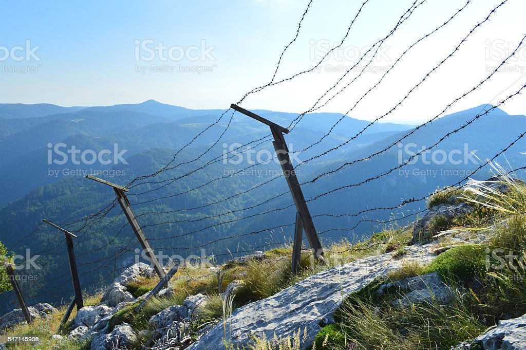 Old barb wired borderline on the mountain height stock photo