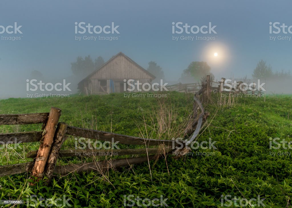 Old barn in the misty morning. The moon was full. Russian village stock photo