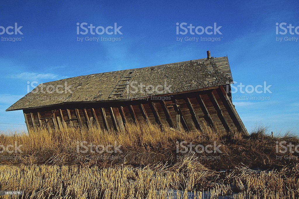 Old barn leaning in the wind stock photo